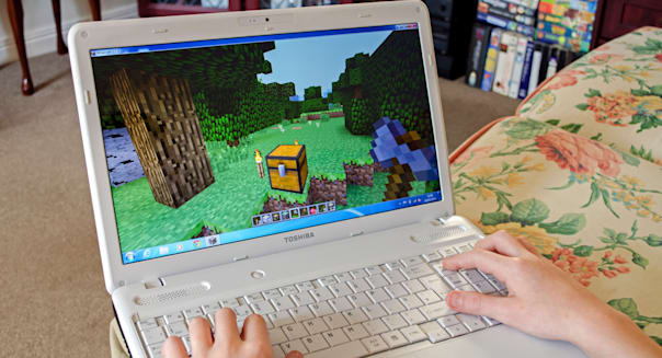 young boy playing minecraft on a laptop computer