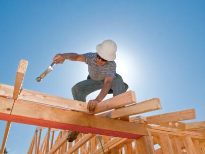 A carpenter installing roof trusses