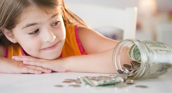 USA, New Jersey, Jersey City, Girl looking at savings in jar