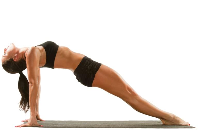 Sexy young yoga female doing yogic exercise on isolated white background