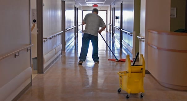 ARTGJN A housekeeping employee mops the floor of a modern hospital