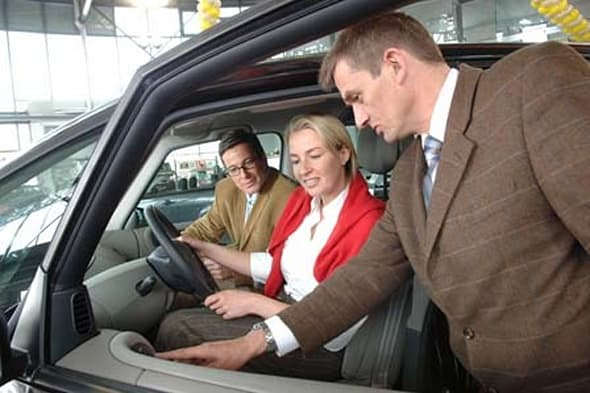 Car dealer with customers