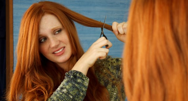 Pretty red head girl nervously cutting hair in mirror