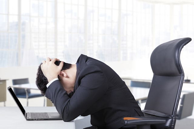Stressful entrepreneur sitting in the office chair with a laptop on the table and holding his head