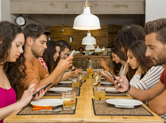 Group using mobile phone at table