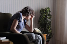 Depressed young woman sitting in chair at home