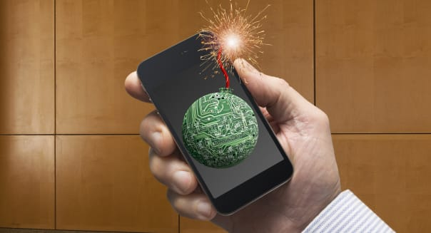 Lit bomb fuse on Caucasian businessman's cell phone