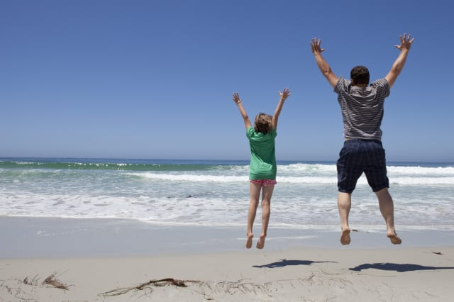 Father and daughter jumping at the