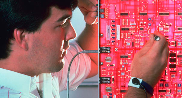 Cellular telephone technician at work on circuit board in Syracuse New York