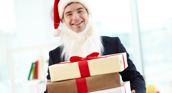 Image of happy businessman in Santa cap and beard holding stak of gifts and looking at camera in office