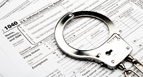 handcuffs on an American 1040 income tax form indicating tax fraud or evasion