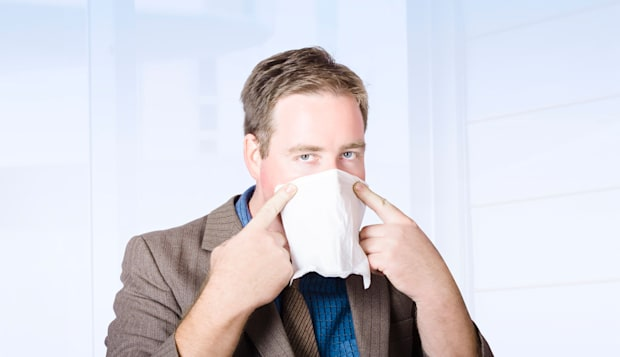 Unwell male office worker suffering from a contagious virus, covering face with tissue during cold and flu season