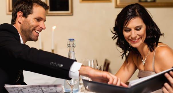 CRJ3GM Couple examining menus in restaurant  couple; examining; menu; restaurant; business; business; carte; du; jour; scrutiniz