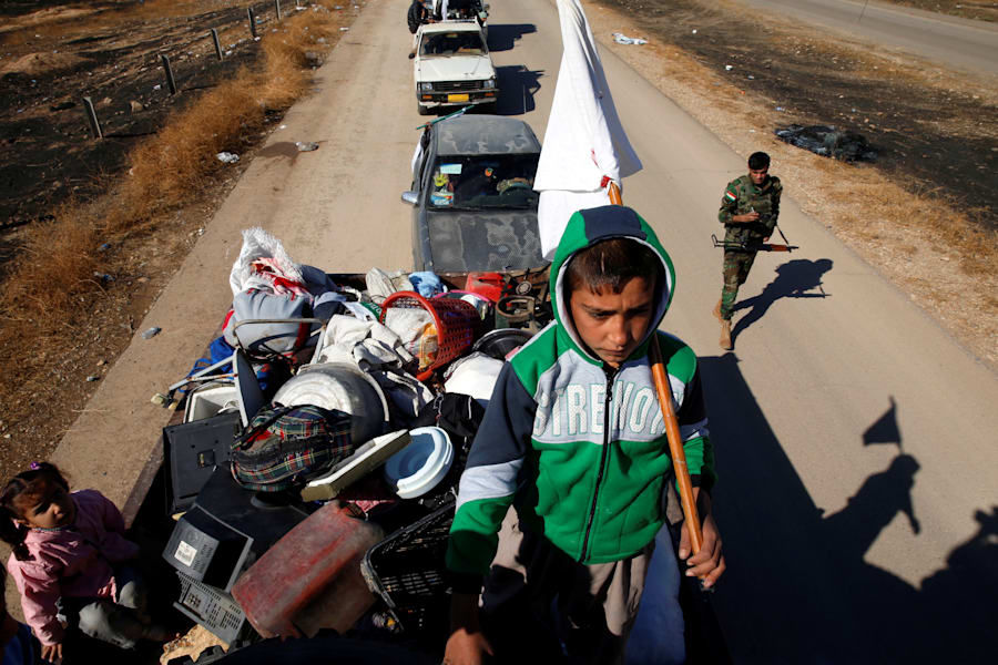 An Iraqi child holds a white flag as he flees with his family from Gogjali village near Mosul during...