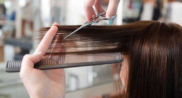 hairdresser cutting client's...
