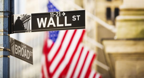 Wall Street sign against New York Stock Exchange, New York City, USA.