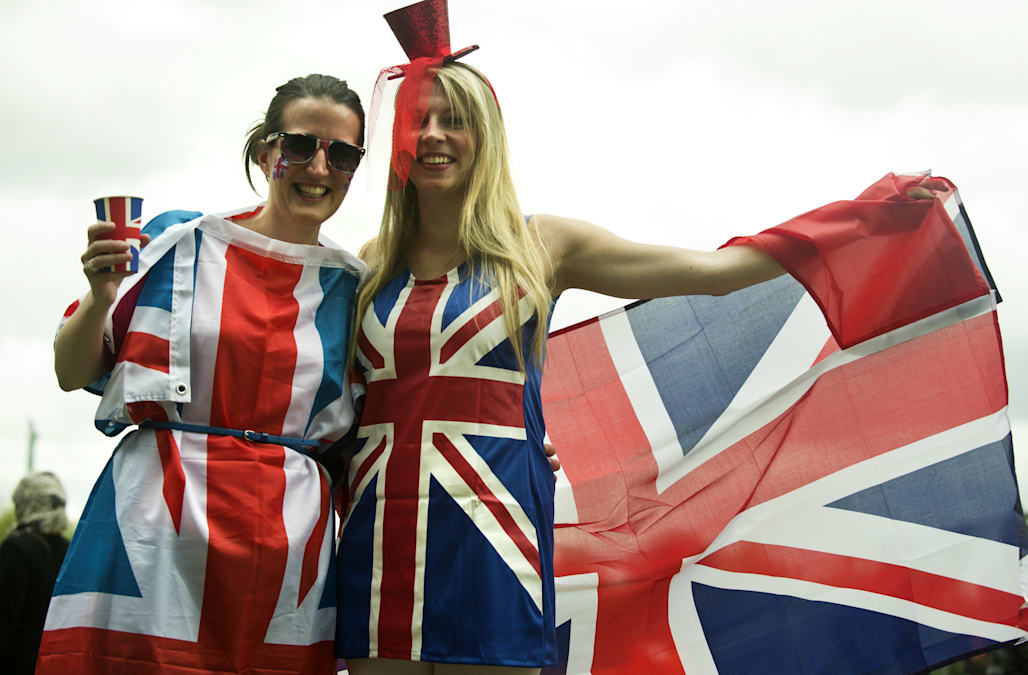 Two women in Union Jack costumes pose as