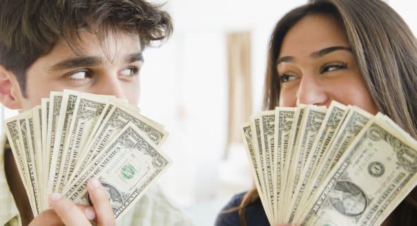 Couple holding handfuls of money