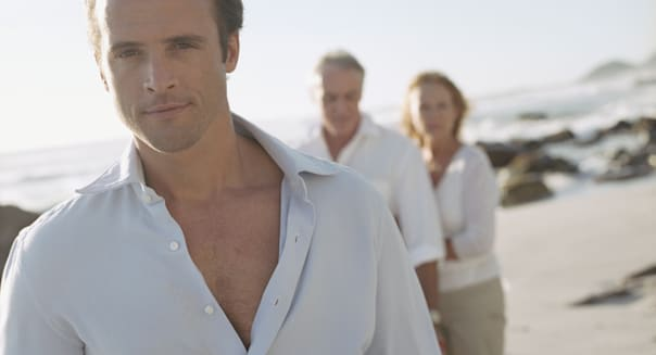 Man on beach with parents in background