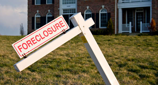 Foreclosure sign in front of a large single family home