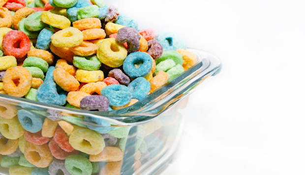 Colorful cereal in bowl on white background