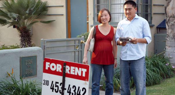 Pregnant Korean couple checks a sign for an apartment to rent