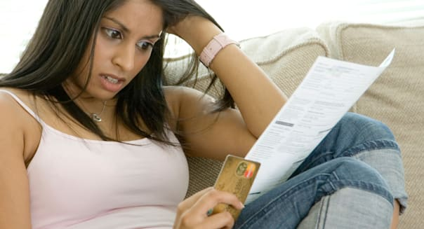 A young woman worried by her credit card statement