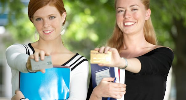 AHMXMT Woman displaying credit cards in park college students credit