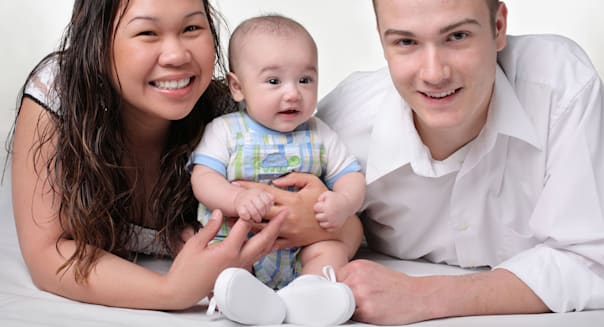young bi-racial parent holding son white background