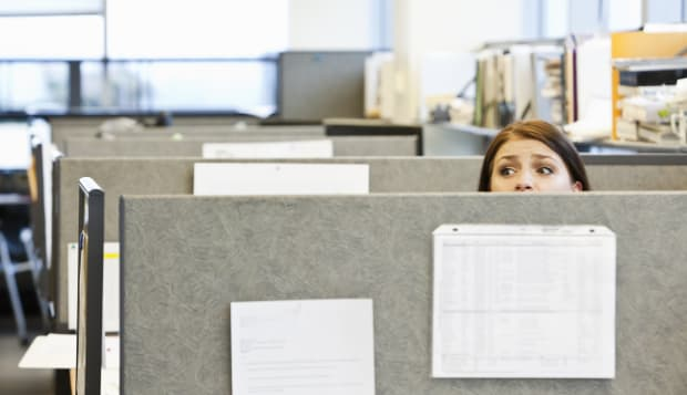 Worried office worker looking over top of cubicle
