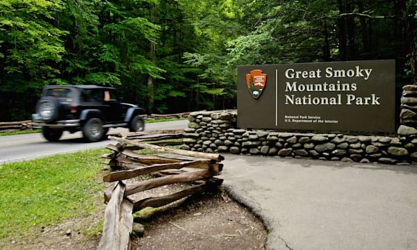Jeep with Motion Blur Driving Past the Entrance Sign to the Great Smoky Mountains National Park on Route 441 in Tennessee