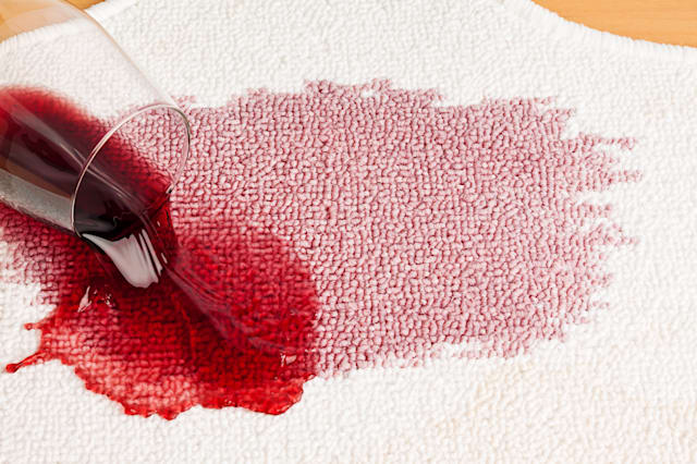 red wine is spilled on a carpet....
