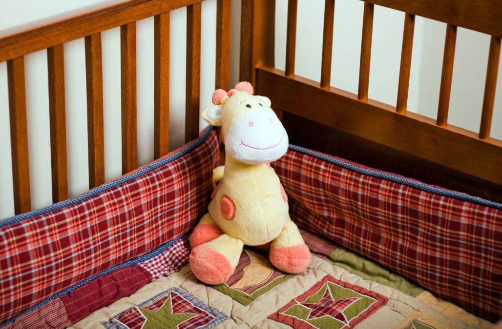 Yellow stuffed animal giraffe in empty baby crib