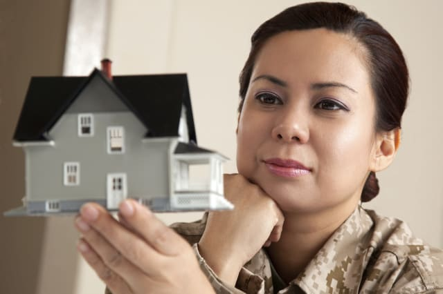 US Marine Female Soldier holding a small house Real Estate concept.