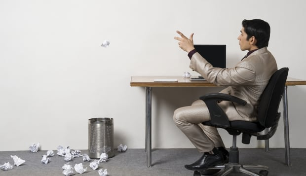 Businessman throwing crumpled paper into garbage bin