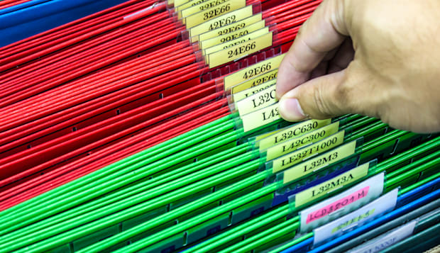 Abstract background image of colorful hanging file folders in drawer. Macro with with extremely shallow dof. Selective focus in