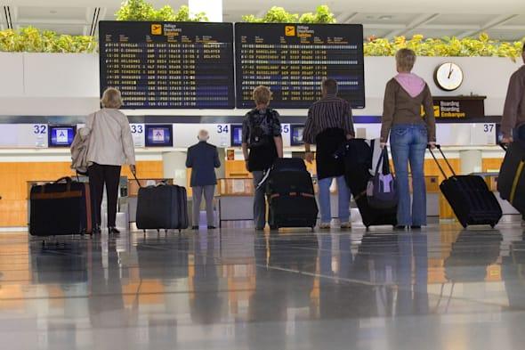 A7BPPF Airport passengers with luggage standing waiting at check in area on concourse looking at flight information boards