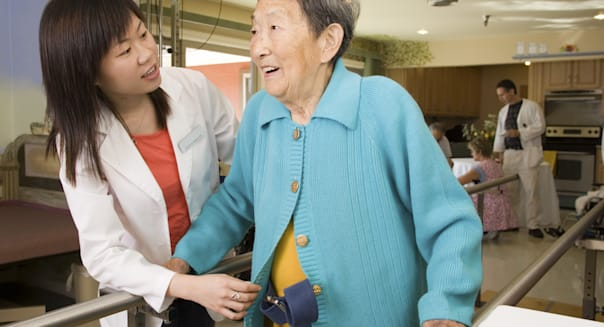 Woman helping patient at rehabilitation center