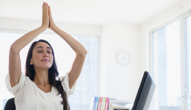 Caucasian businesswoman meditating at desk