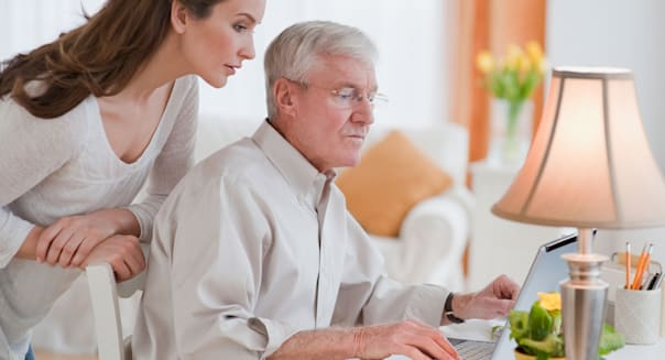 Daughter helping senior father with computer