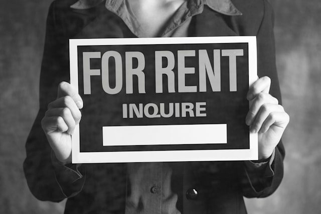 Woman holding up a For Rent sign