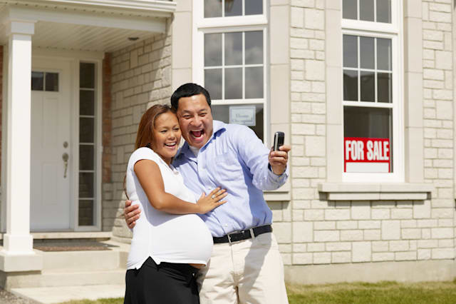B3A0P9 Pregnant Asian couple in front of new house