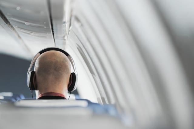 Businessman sitting on aeroplane seat, wearing headphones, rear view