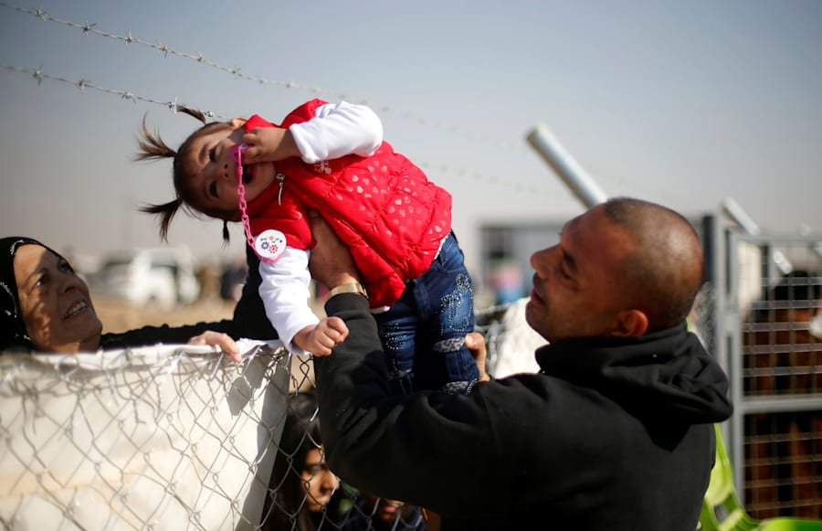 A displaced Iraqi man, who fled the Islamic State stronghold of Mosul, holds his daughter to be seen...