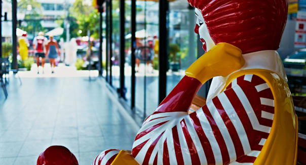 Sitting figure of Ronald McDonald in Thailand with departing customers. Thailand S. E. Asia