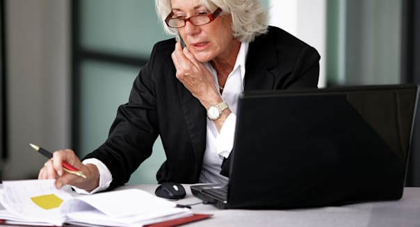 Portrait of a senior woman in suit in front of a laptop computer