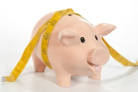 An empty piggy bank looks anxiously at the camera, hoping for its first deposit as a tape measure is wrapped around its body. Th