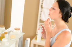 Young woman in bathroom clean face make-up removal looking mirror