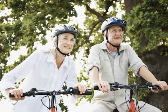 Retired couple staying fit by cycling together in the woods