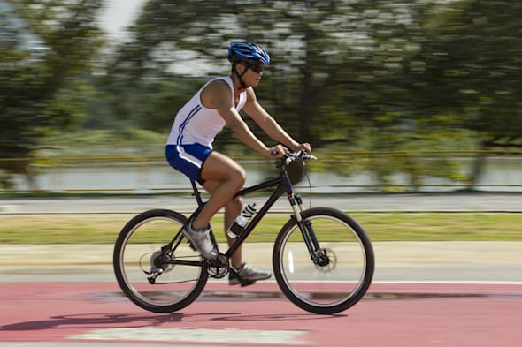 Asian male Cyclist training on a road